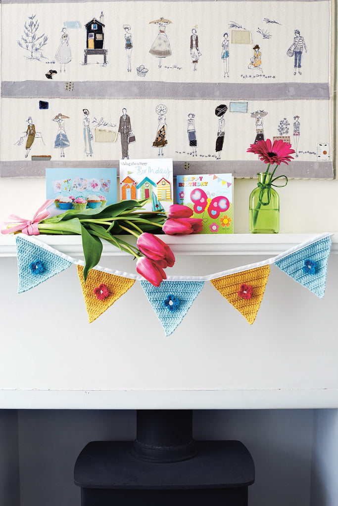 Crocheted bunting with flower motif on each pennant
