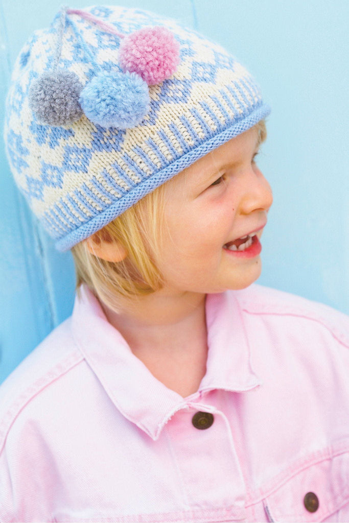 Patterned knitted winter hat for a girl with three pom-poms