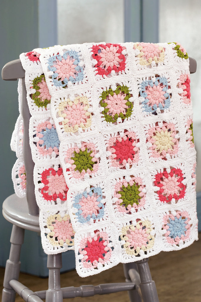 Crocheted granny square throw in pretty pastel colours