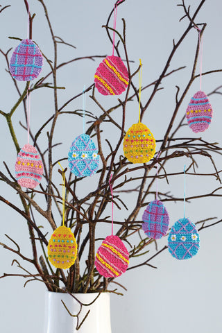 Vase of crocheted egg-shape decorations hanging from twigs