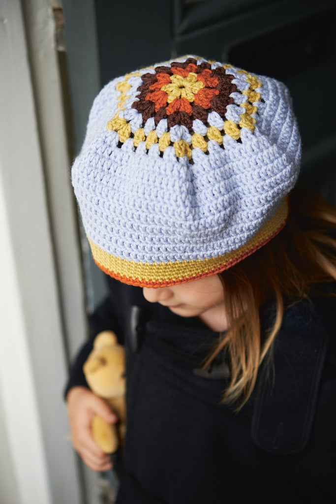 Child's crocheted beret with circular floral crown and striped border