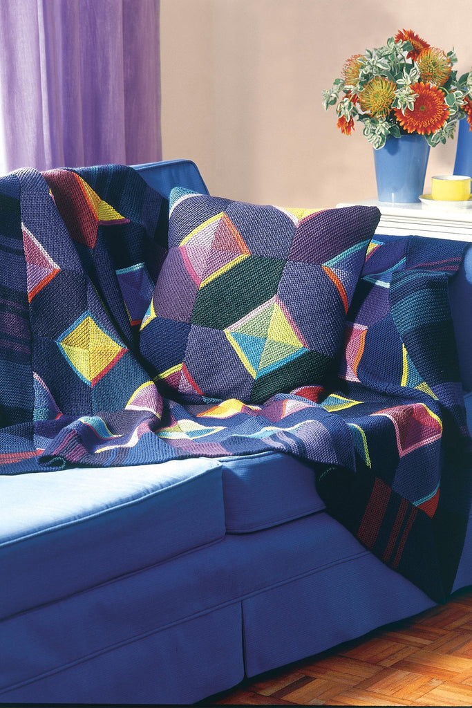 Bold knitted blanket and cushion with triangles within squares in different colours