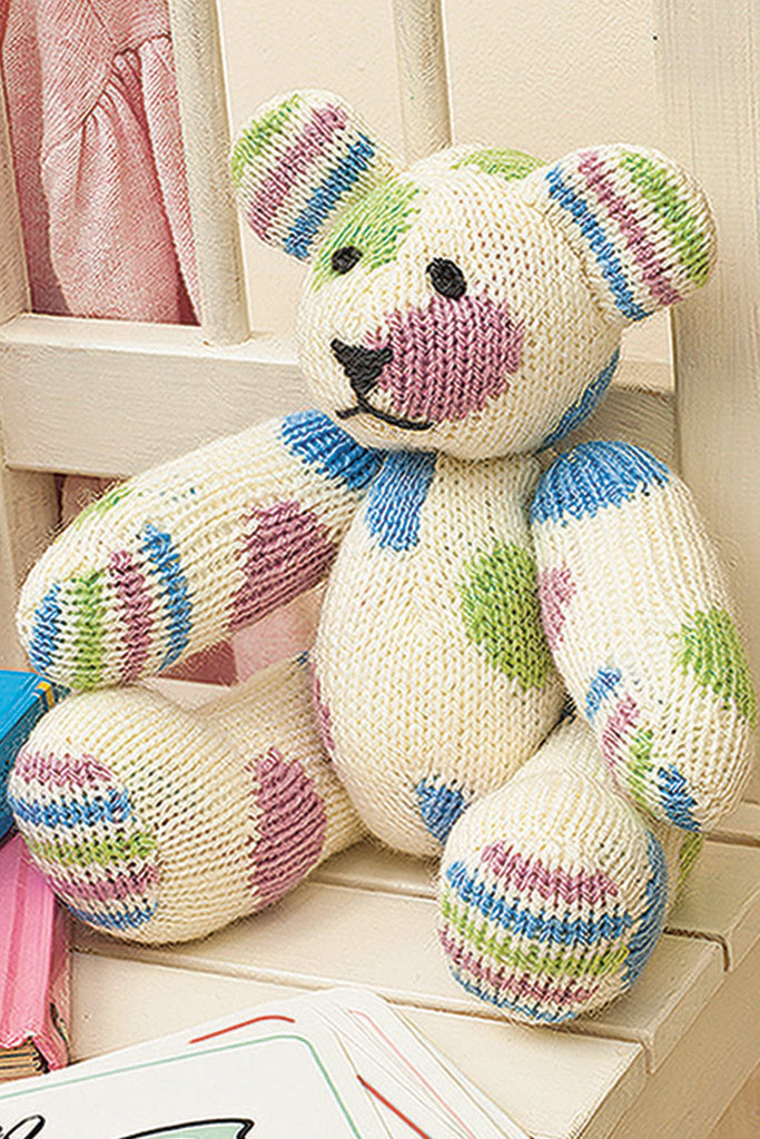 Knitted pastel-patterned teddy bear toy