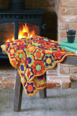 Crocheted hexagon blanket in bright orange, green, yellow and purple