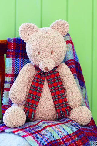 Crocheted cuddly toy teddy bear with tartan scarf