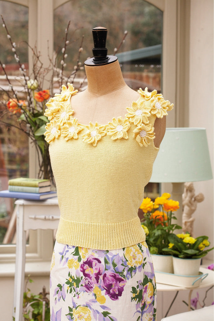 Retro women's sleeveless crocheted sweater with flower motifs around neck and shoulders