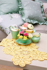 Crocheted table mat with six joined flower patterns in lemon yellow