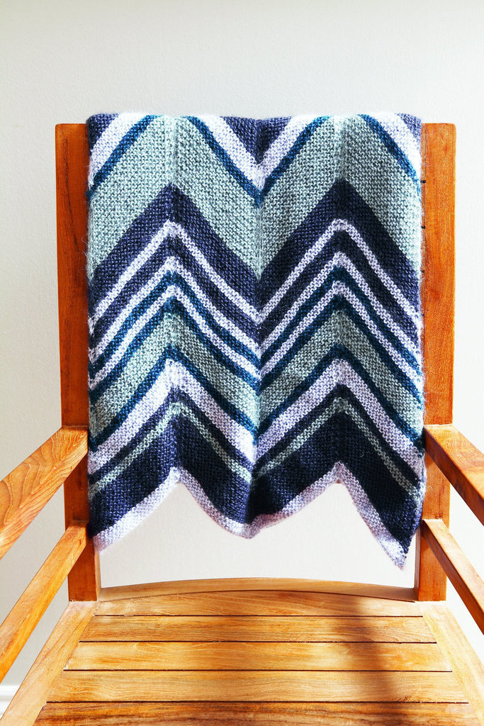 Bold knitted zig zag pattern blanket with deep V design in shades of blue