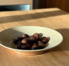 Chestnuts in white ceramic bowl on table