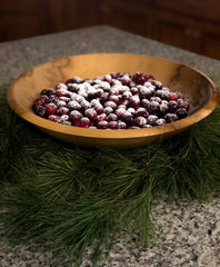 Christmas scene with wooden bowl filled with sugar dusted cranberries on evergreen bough