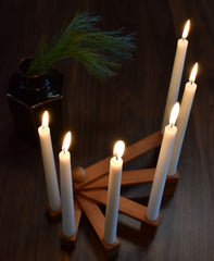 Wooden candle holder lit on table in dark room
