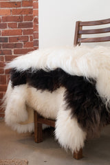 Stack of white and brown sheepskins on walnut dining chair