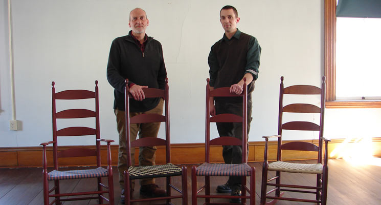 "Brother Arnold Hadd and Adam Nudd-Homeyer with the original and ""new generation"" of Alfred Chairs. Photo: United Society of Shakers"
