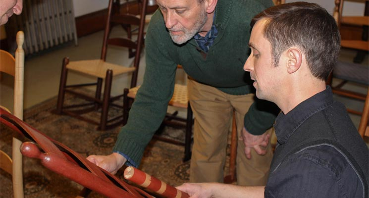 Brother Arnold Hadd and Adam Nudd-Homeyer examine one of the original Alfred Chairs and discuss paint selection. Photo: Sean Hurley