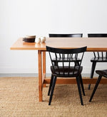 Ceramic plates and cups on modern cherry trestle table with four black modern windsor stye Boston chairs on beige woven rug with white background