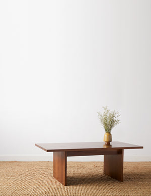 Walnut coffee table with trestle panel style legs on beige woven rug with white background
