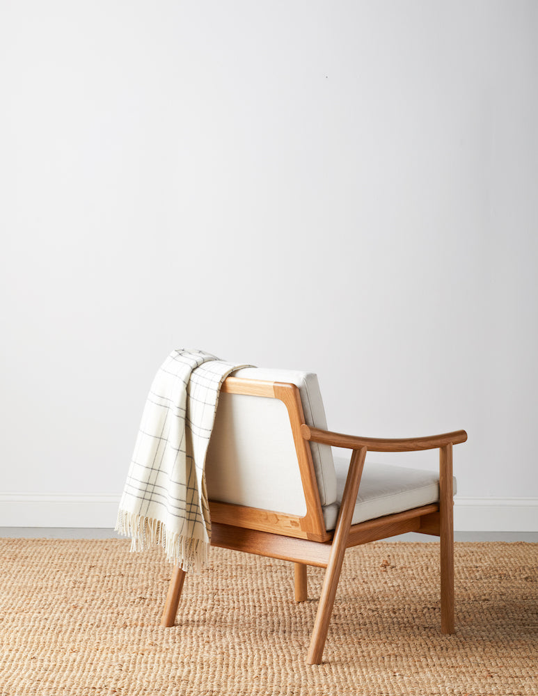 White oak Scandinavian style lounge chair shown from back with open wood frame back, Knoll fabric cushions in Buff, and cream checkered blanket draped over the back