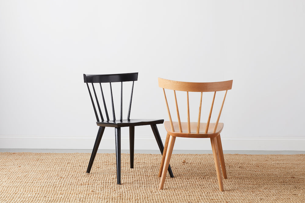 Two modern Windsor inspired spindle chairs, one painted black and one in white oak
