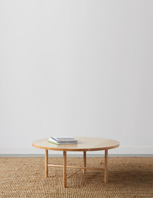 Round, maple wood, Scandinavian inspired coffee table with round legs on beige woven rug with table top magazines and white background