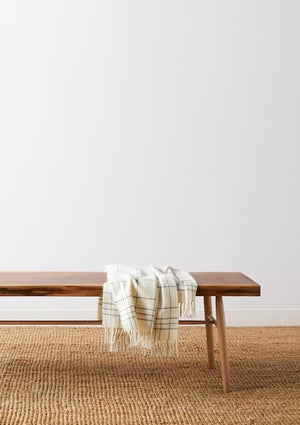 Walnut live edge bench with cream checkered throw blanket on beige woven rug