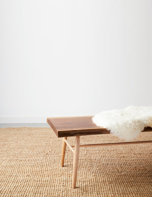 Walnut live edge bench with maple round turned legs with white sheepskin cushion on beige woven rug