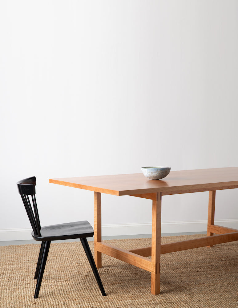 Ceramic bowl on modern cherry trestle table  with visible joinery with black modern Boston chair on beige woven rug with white background