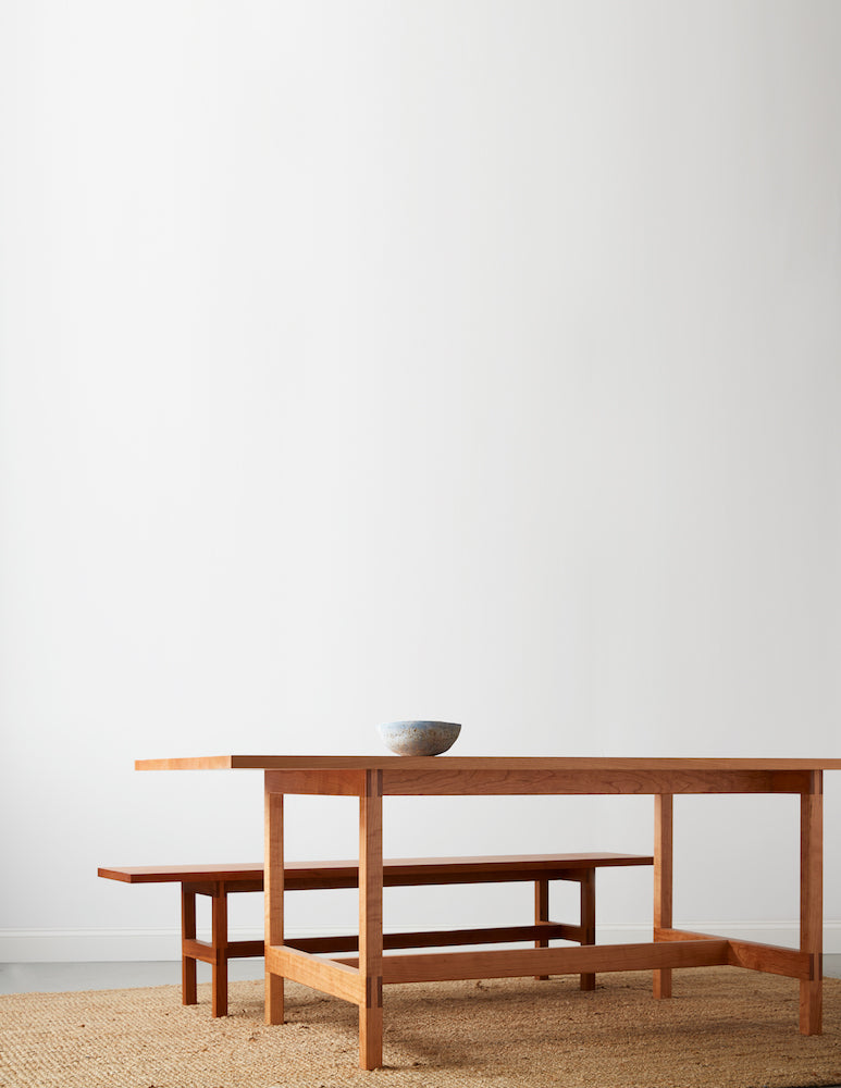Modern trestle table and bench in solid cherry with pottery bowl on beige woven rug with white background