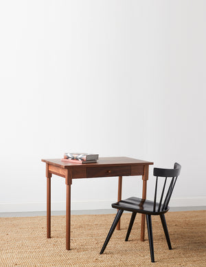 Small walnut MS1 desk with rounded legs and books on top paired with black modern windsor inspired spindle chair