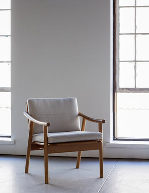 White oak lounge chair with rounded legs and curved arms with Knoll fabric cushions in front of large industrial windows