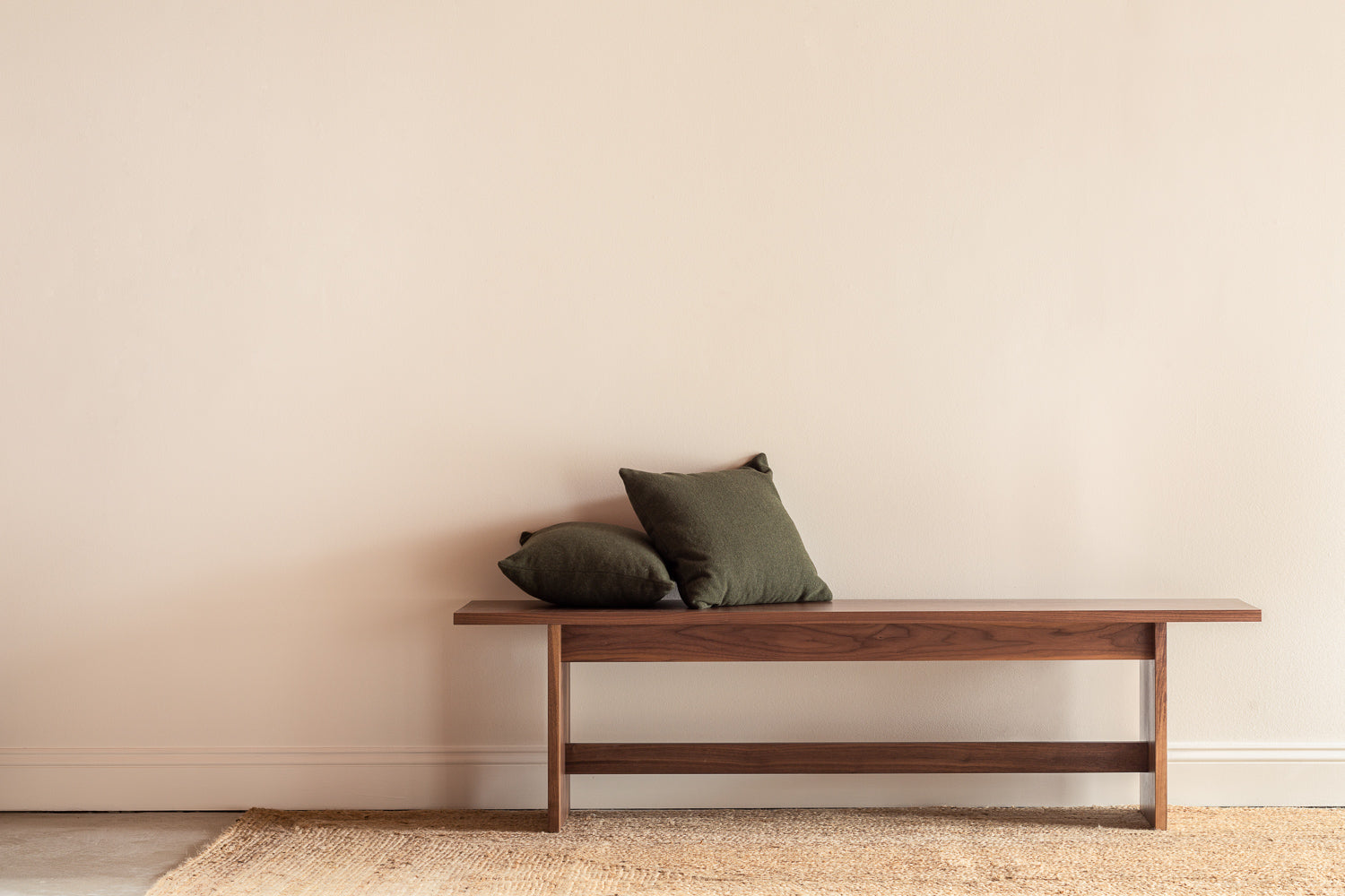 Modern Scandinavian inspired Hygge Bench in walnut with two green pillows along blank wall