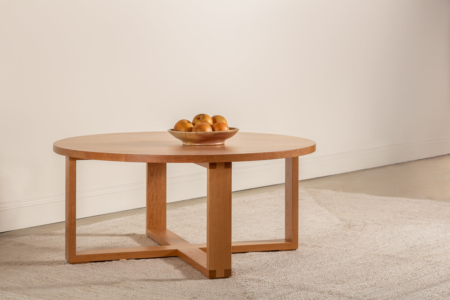 Round Lokie coffee table shown in cherry with blow of fruit