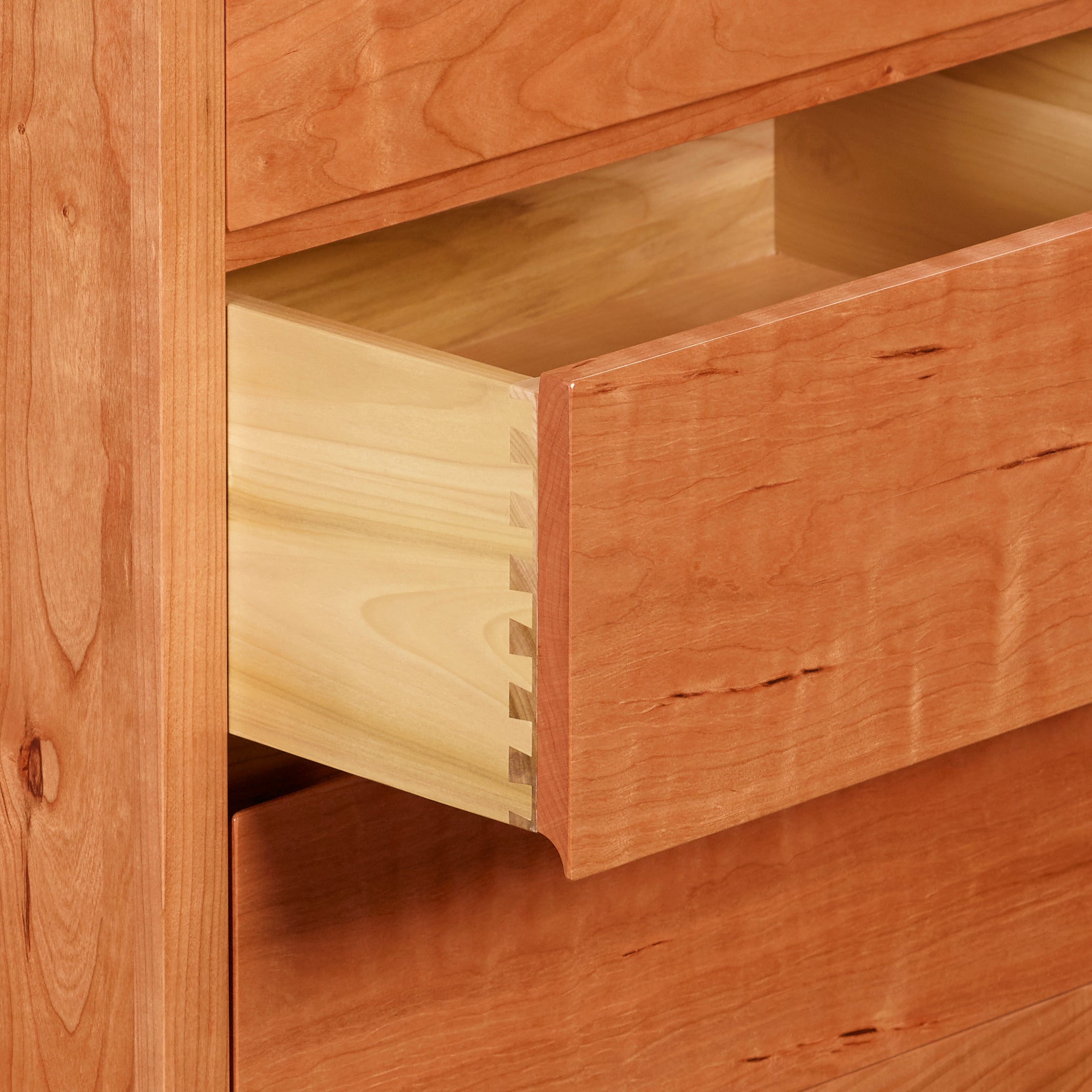 Open drawer of cherry Acadia bedroom storage dresser showing dovetail joinery