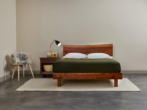 Bedroom furnished with Acadia nightstand, live edge bed in walnut, maple bistro chair and cozy styling