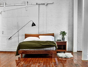 Modern industrial bedroom with white brick walls and walnut Acadia nightstand and live edge bed