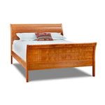Modern take on Victorian era sleigh bed, with curved headboard and footboard, in cherry wood