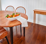 Clean dining room furnished with solid cherry furniture, including Shaker Hall Table, and styled with bowl of oranges