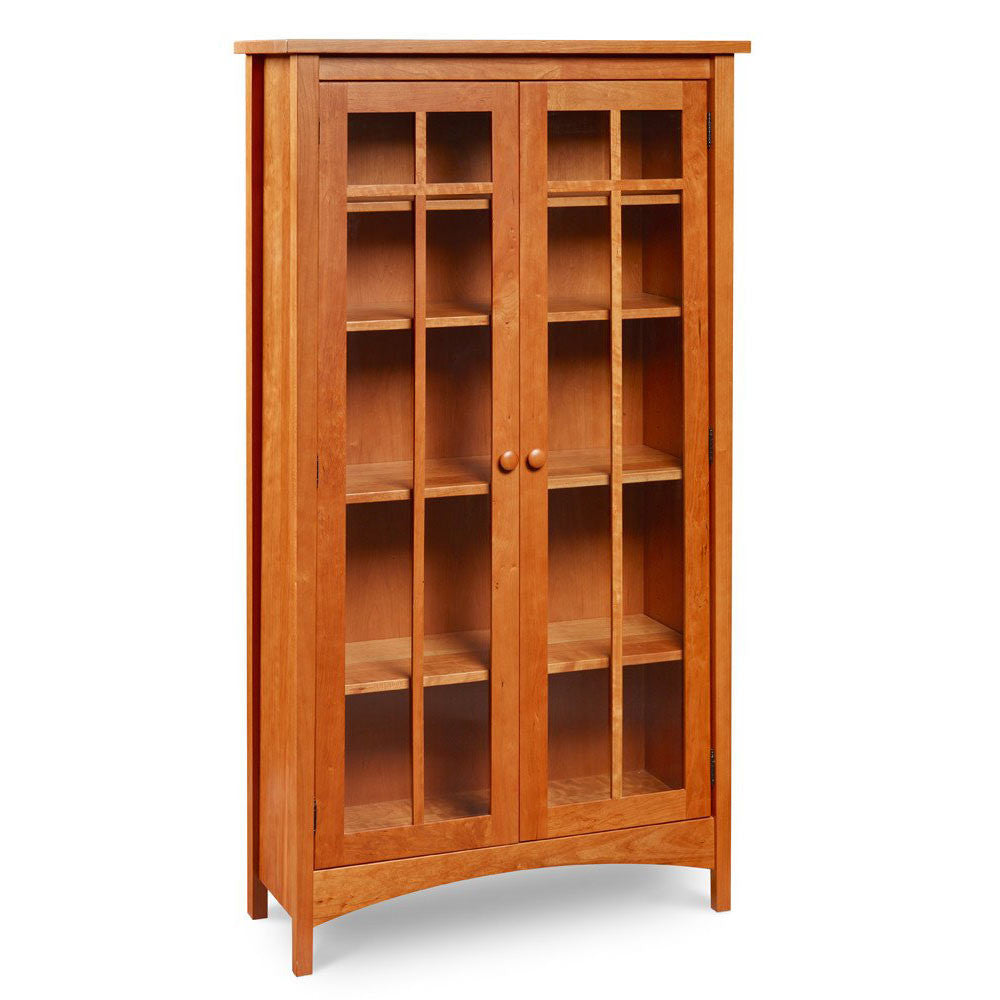 Arts and Crafts style solid cherry bookcase with arched apron, glass doors and five storage shelves