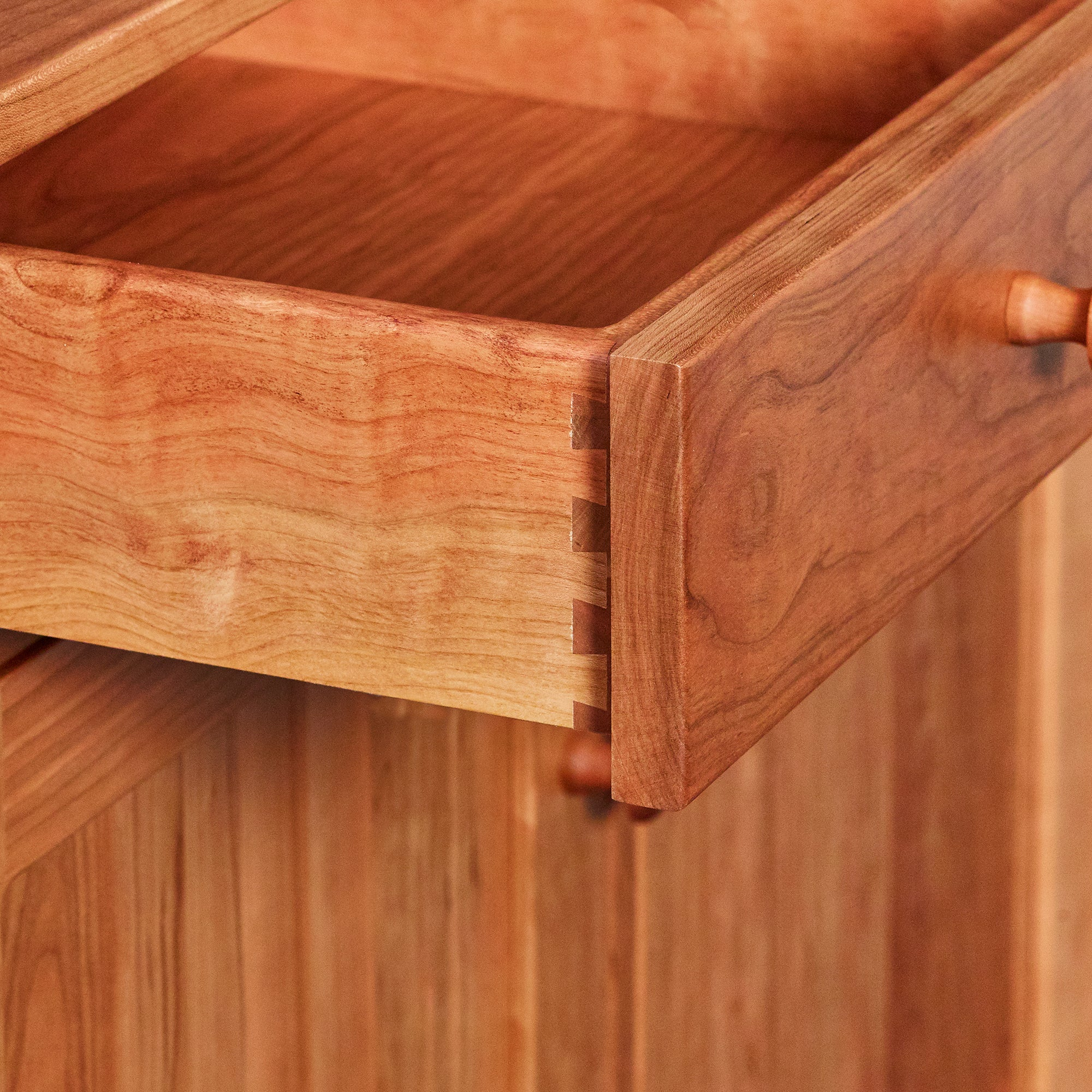Cherry wood drawer showing dovetail joinery and Shaker knob details