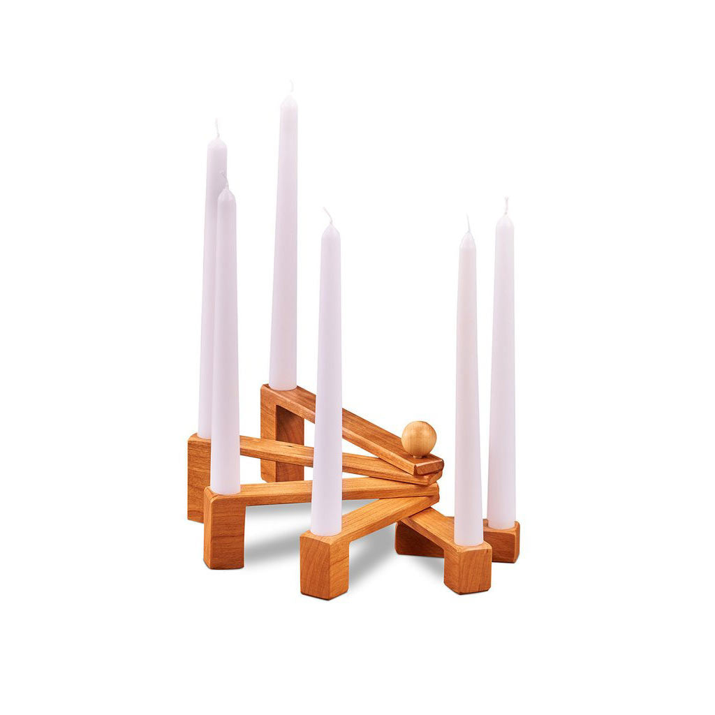 Collapsible candle holder with six cherry wood pivoting, nesting holders with six white taper candles