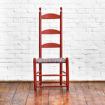 Traditional Shaker side chair in red paint with tall three slat ladder back and taped seat in front of white brick wall