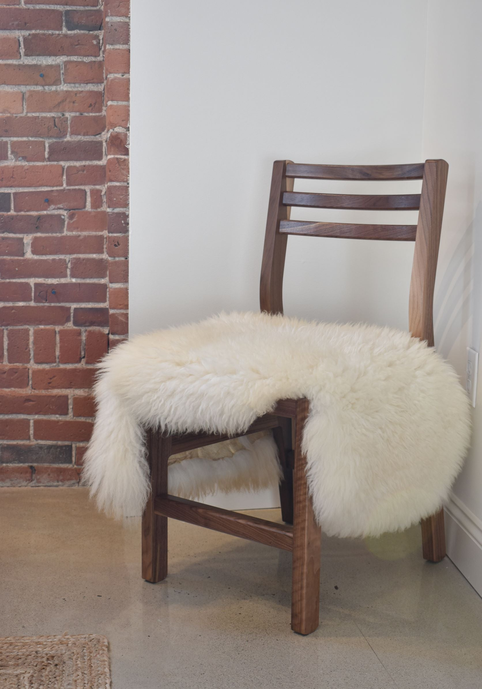 Solid walnut wood dining chair with white sheepskin throw on seat
