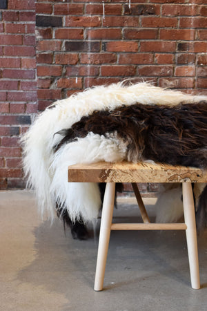Solid wood bench with pile of white and brown sheepskin throws