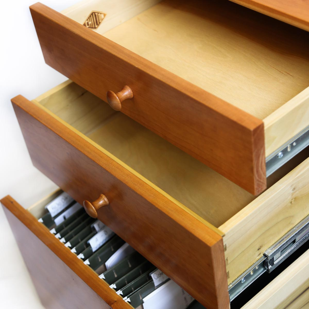 Three opened desk drawers holding files