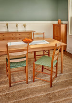 Neutral colored dining room with Shaker sideboard, cabinet, table and taped seat chairs, all made of cherry wood