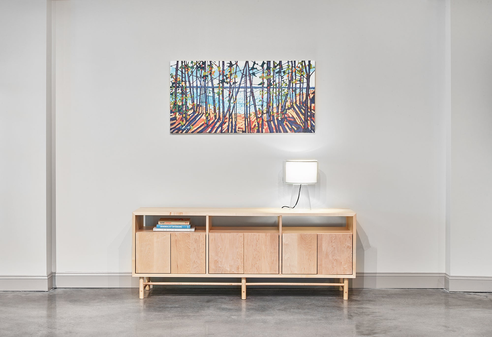 Industrial room with mid-century modern Navarend media case in solid maple with round legs and stretchers and an impressionism painting of trees