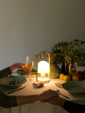 Dining Table set with dinner, glowing Follow Me cordless lamp, and two people holding hands