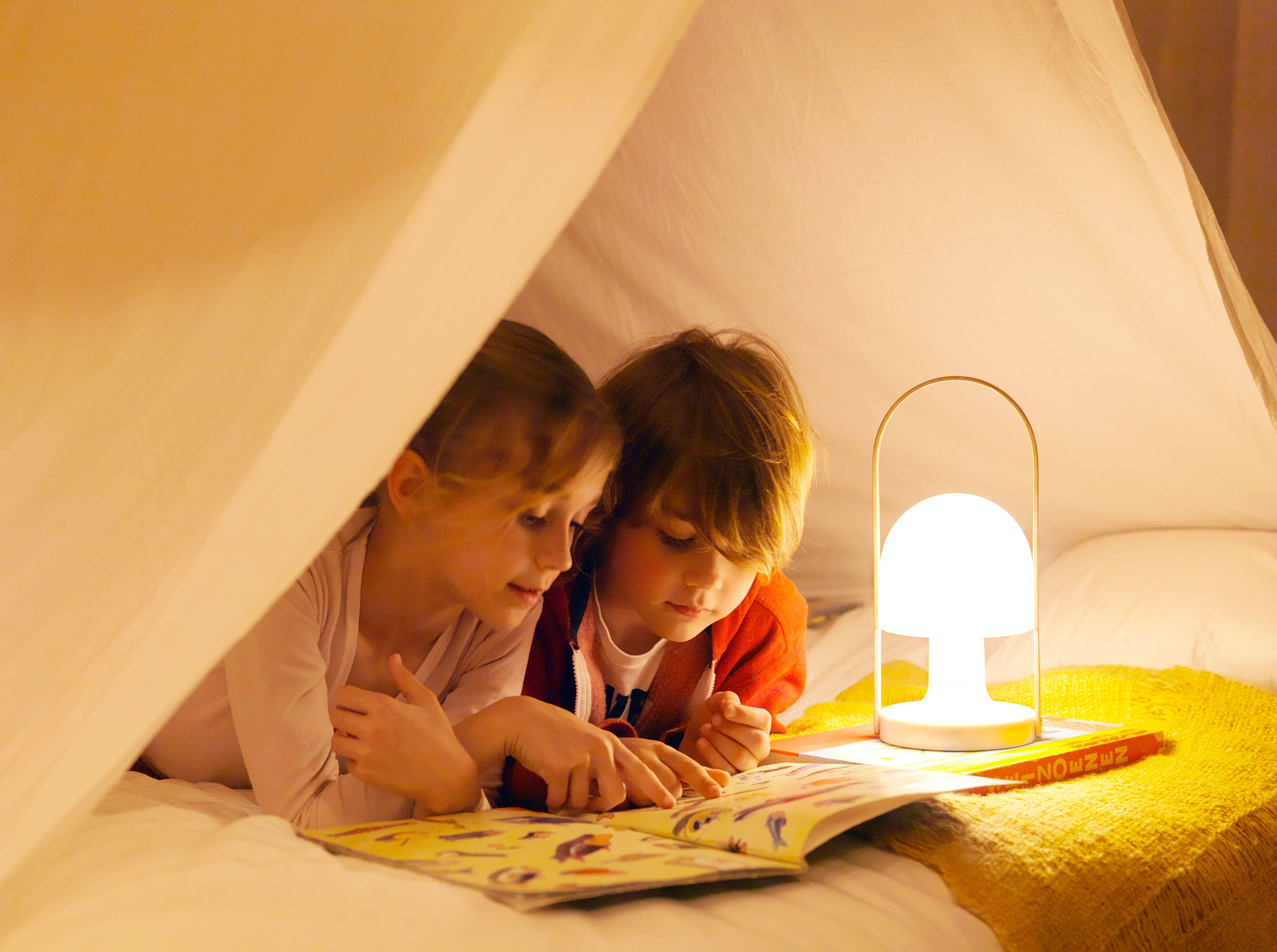 Indoor children's play tent with two kids reading to the light of the Follow Me portable lamp