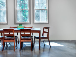 Sunny industrial style dinning room furnished with mid-century modern table and chairs in walnut