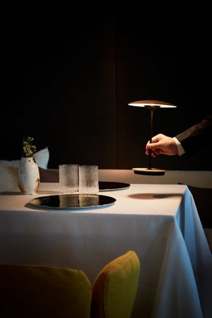 Waiter placing portable white oak Ginger table lamp on set restaurant dining table