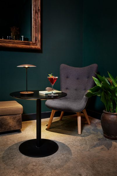 Dark and cozy corner of room with black pedestal table with portable Ginger table lamp next to grey lounge chair